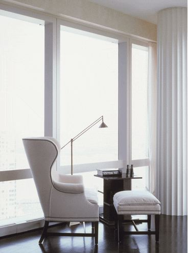 A white wingback chair and ottoman make for a sleek and stylish window seat in a city apartment with dark wood floor and wall to ceiling windows