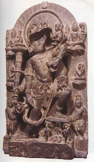 Vishnu as Varaha, the boar avatar, ascending from the ocean depths. In the crook of one of his left arms he bears the rescued goddess Bhumi or Prithivi, the earth. From above Brahma (right) and Shiva (left) look on, while human worshippers pay homage. Chauham style slate carving, twelfth century. Victoria and Albert Museum, London.