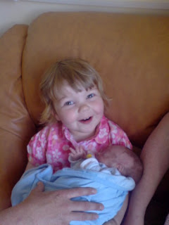 Photo of smiling little girl holding her baby brother for the first time