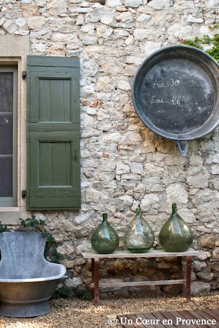 Dans un patio, mise en scène avec des vieilles bombonne et un ancien receveur de douche en zinc