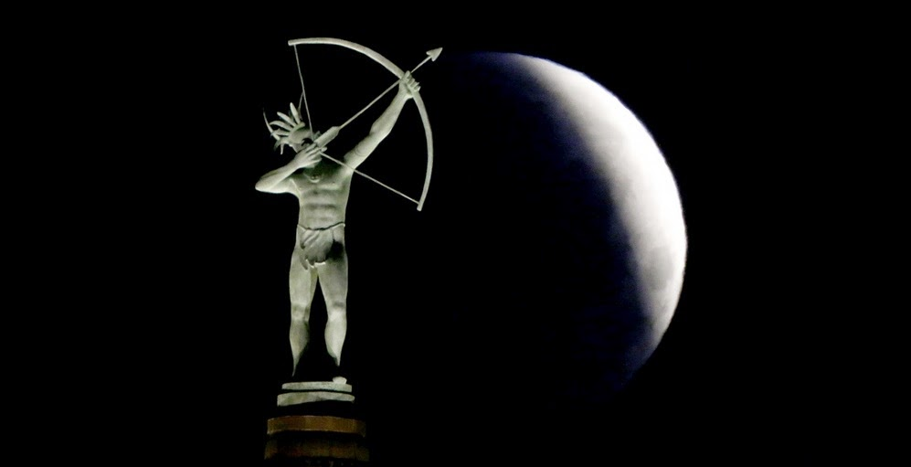 A partially eclipsed moon looms behind a statue of a Kansa Indian at the Kansas Statehouse in Topeka, Kan. The moment when the moon was completely obscured by Earth's shadow lasted several minutes, making it the shortest lunar eclipse of the century. Charlie Riedel/AP