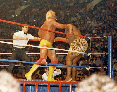 Hulk Hogan has white powder on his thigh and knee pad after pulling it out of his trunks and throwing it at Kamala. Toronto WWF Referee John Bonello is admonishing Hulk, even in this no-DQ match.