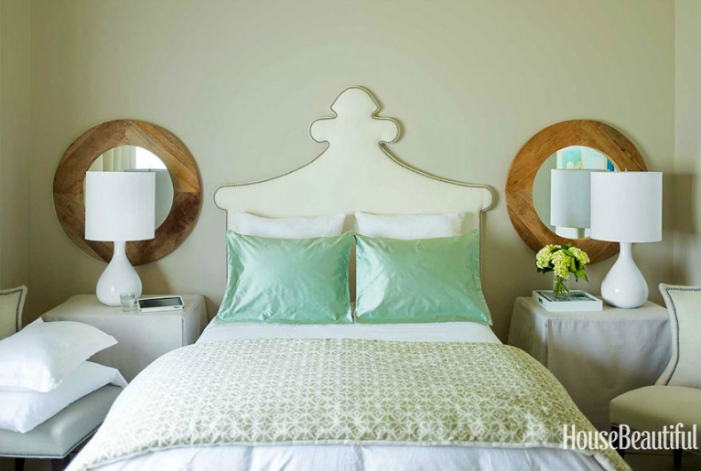white upholstered heaboard and seafoam green coastal pillows, wood round mirrors