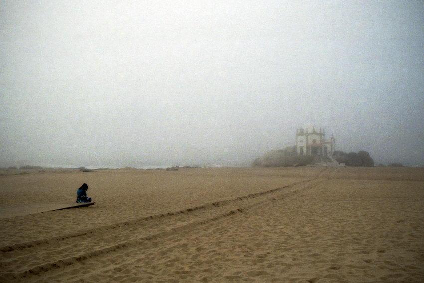 Foto em dia de nevoeiro. A Capela à direita, pouco visível e uma mulher à esquerda, em primeiro plano, sentada na areia da praia