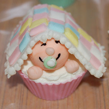 Baby shower cupcake with small baby under towel accessory