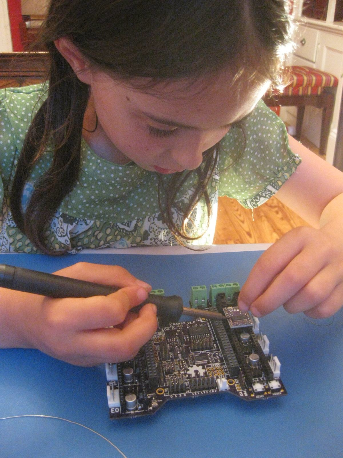 Violet soldered the header pins into the Pololu driver daughterboards.