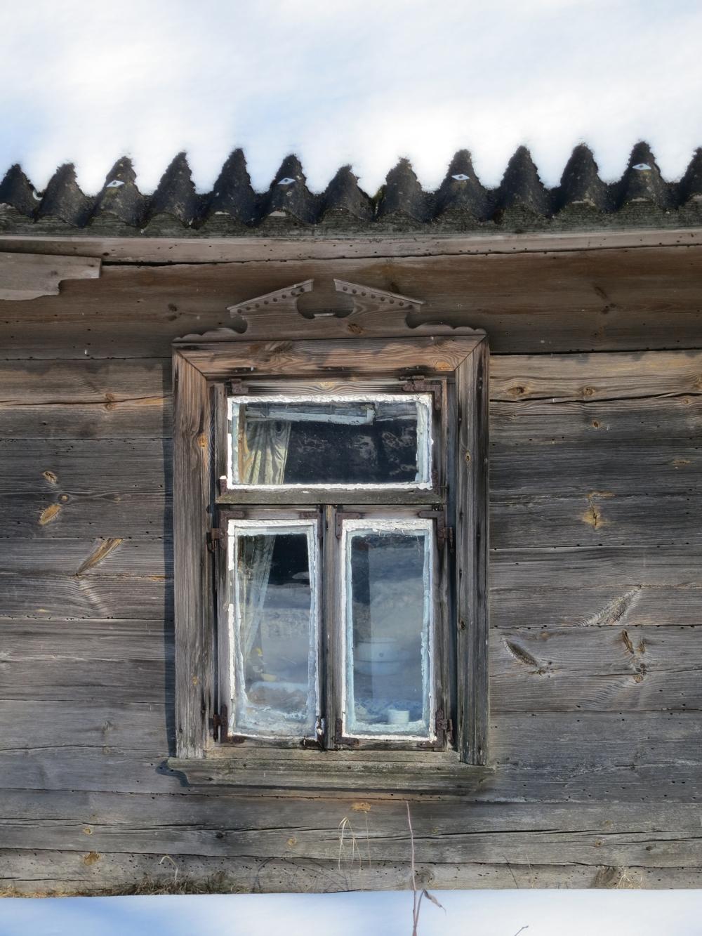 detal okna w drewnianej chacie, znajdującej się w Harkawiczach, okap z czapą śniegu tworzy piękny zygzakowaty wzór