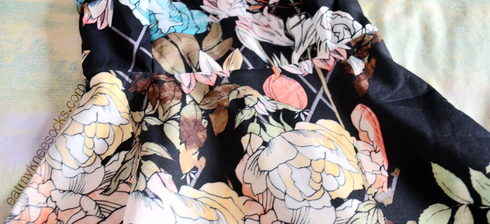 Close-up of the intricate floral pattern on the black sleeveless skater dress from SheInside!