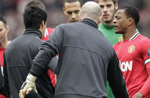 Patrice Evra reacts after Luis Suárez ignored his handshake