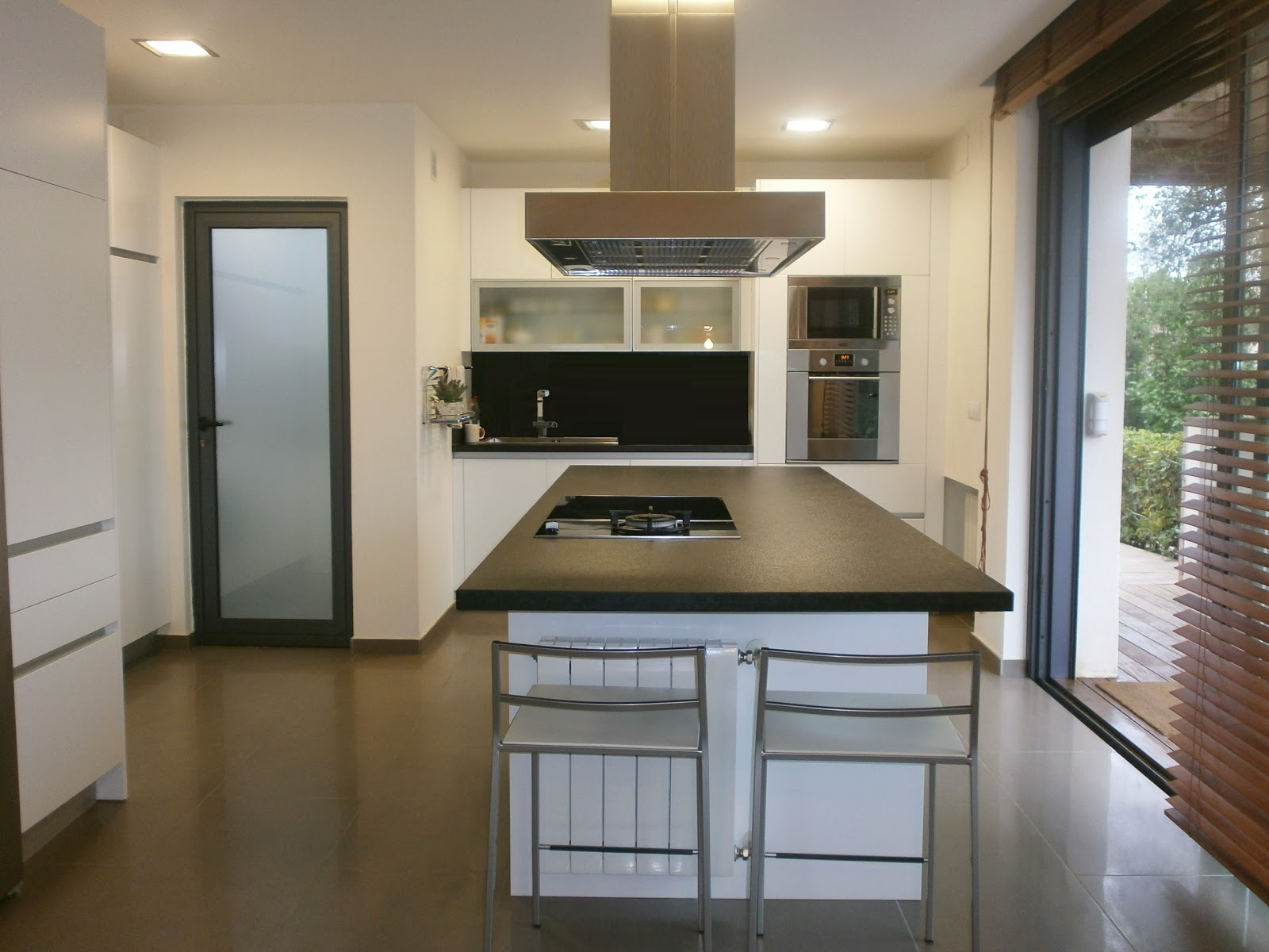 Granito negro y cocina blanca sobria y siempre actual for Diseno cocinas con isla central