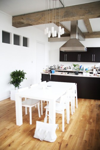 open kitchen with black cabinets, a white dining room table with matching chairs and pendant lights