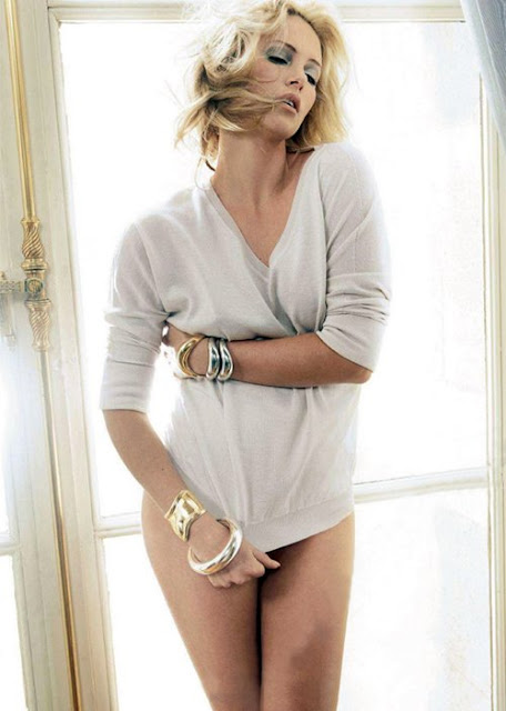 Charlize Theron posing in front of a window