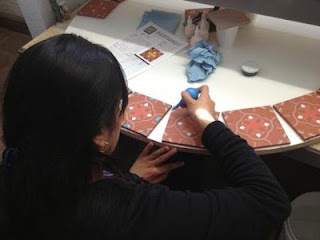 Tile artisan hand-glazing each piece