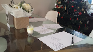 Photo of letters on a glass table with a Christmas tree in the background.