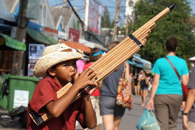 Enfant thai jouant de la fulte à Chatuchak Market