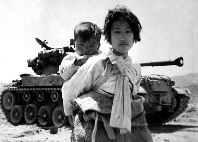 Chica coreana con bebé a la espalda enfrente de un tanque durante la Guerra de Corea