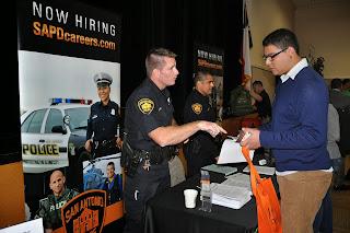 Student talks with San Antonio Police recruiter.