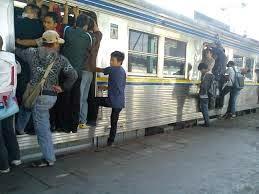 naik di pintu Kereta Commuter Line di saat penuh