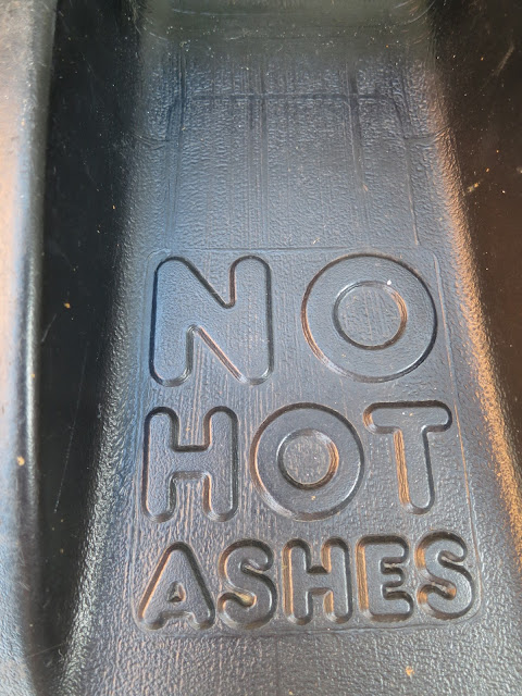 Black plastic dustbin lid with words 'NO HOT ASHES'