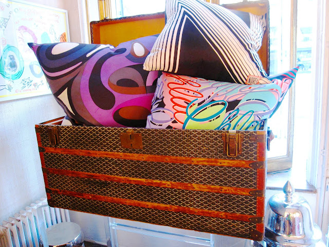 Three brightly colored pillows in a vintage Goyard steamer trunk