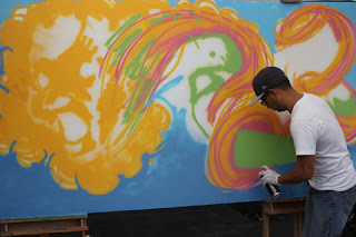 Graffiti Artist Jon using yellow, orange, blue and magenta.