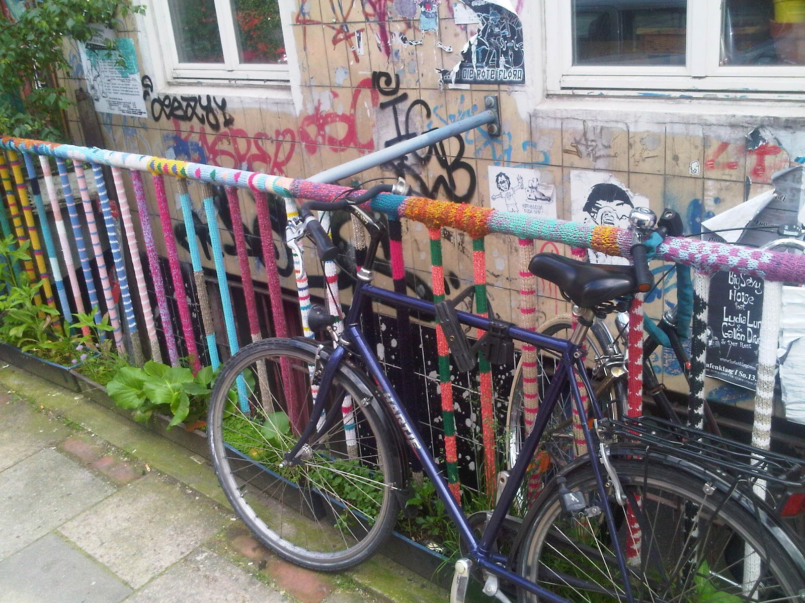 Guerilla Knitting auf St. Pauli. Stahlgeländer mit Strickwaren verkleidet. Fahrrad vor dem Geländer.