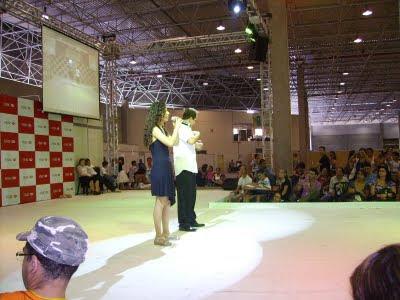 No centro do palco da Reatech, Sara canta e Fabiano Campos acompanha em LIBRAS