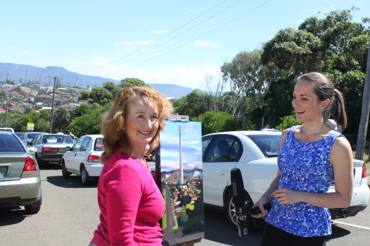 Industrial heritage artist Jane Bennett being interviewed with plein air painting of Port Kembla Copper Copper Stack