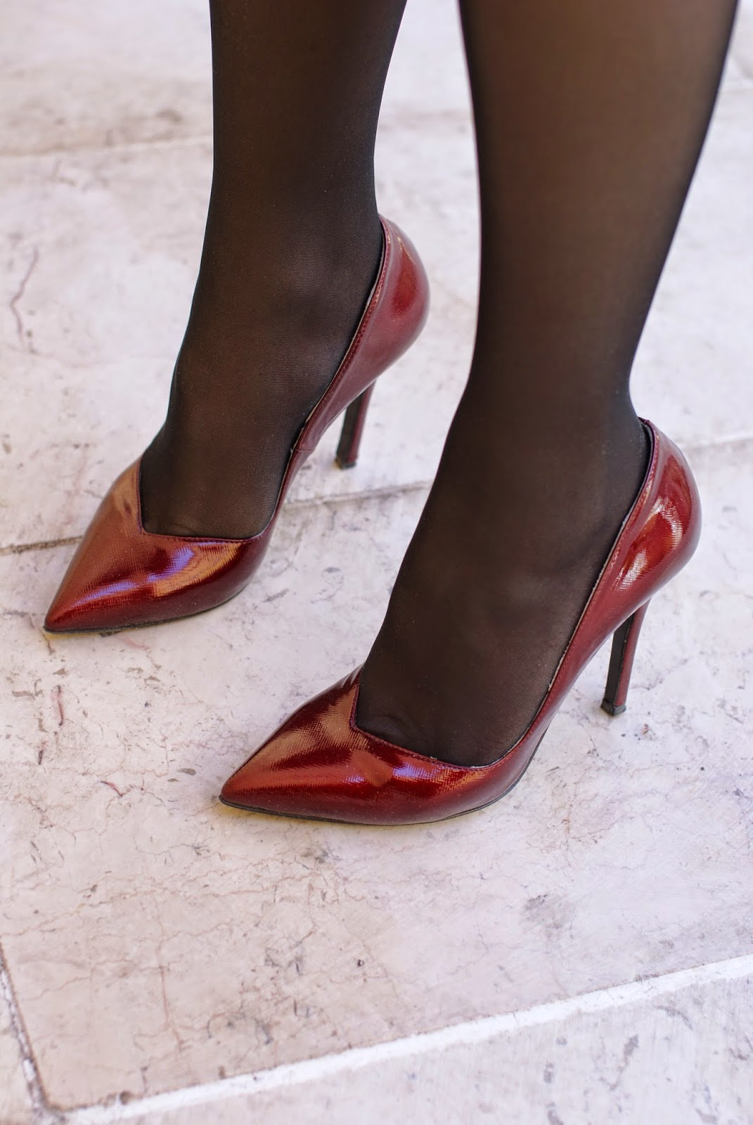 Red patent leather stiletto pumps worn with black sheer tights