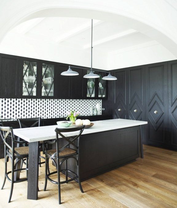 Kitchen with dark cabinets with diamond shaped molding details, light