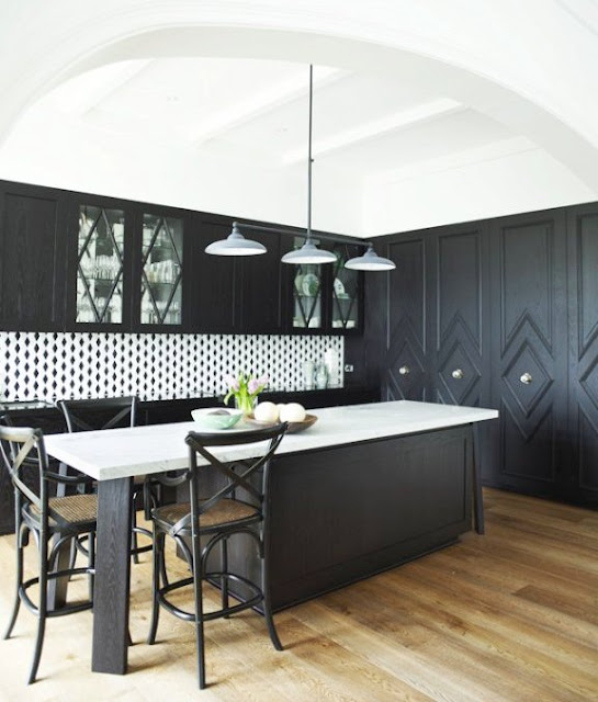 Kitchen with dark cabinets with diamond shaped molding details, light rustic looking floors, a very bold trellis pattern black and white backsplash and glossy black counters. The island in the center has a glossy white counter top.