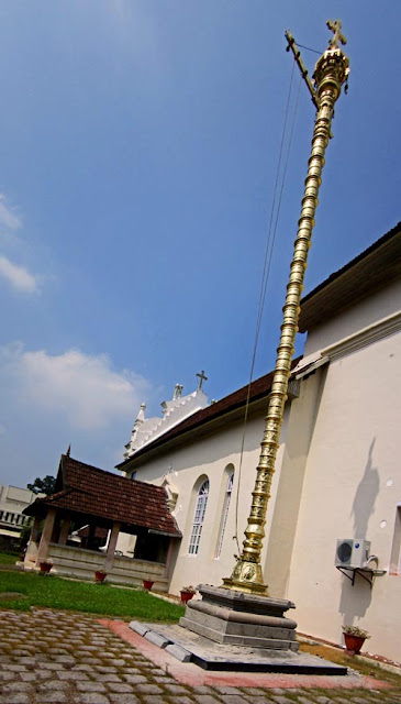 tall gold lamp tower at the entrance to the Kerala ancient church of Cheriya Pally
