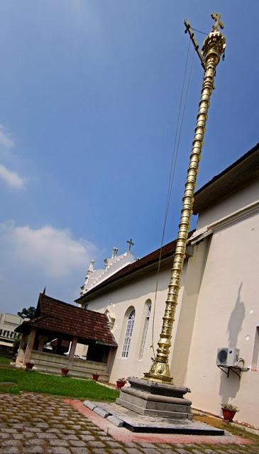 tall gold lamp tower at the entrance to the Kerala ancient church of Cheriya Pally