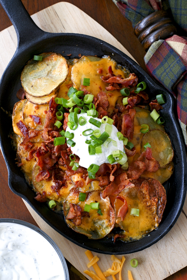 Loaded Potato Nachos are made by topping oven roasted potato rounds with all of your favorite loaded baked potato toppings, nachos-style!