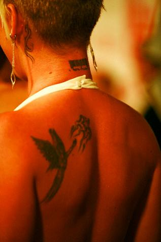 fairy chasing a shooting star tattoo on woman's upper back.