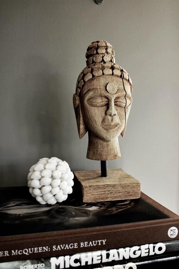 buddha, trästaty, träfigur, trä buddha på fot, more, varberg, snäckor, love warriors, webbutik, böcker till stilleben, grå vägg, interiör, detaljer på skänk, svart plåtskåp, vardagsrum,