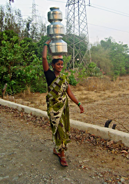 woman carrying steel pots on head