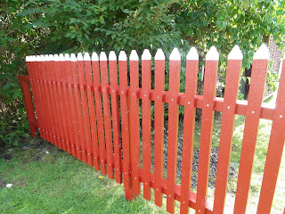 rött staket med vita toppar