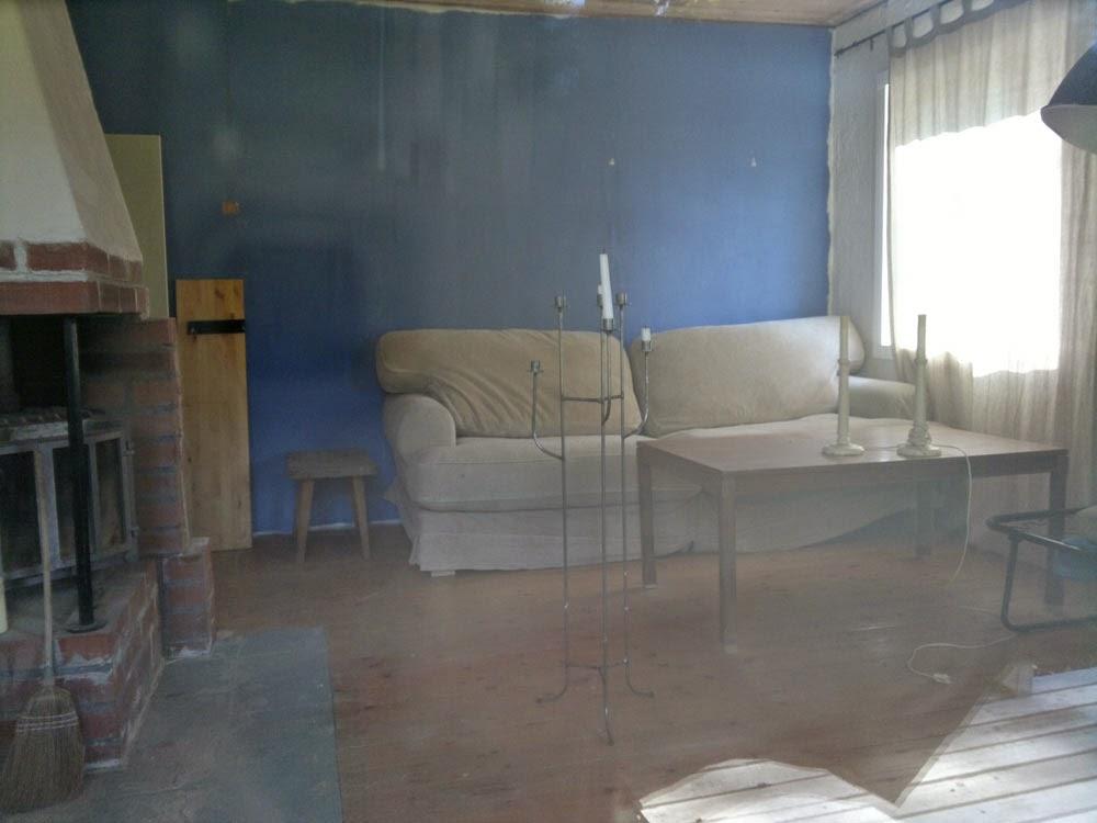 En soffa längs med ena väggen och några ljusstakar, ser rätt mysigt ut! En smula av eldstaden syns till vänster.