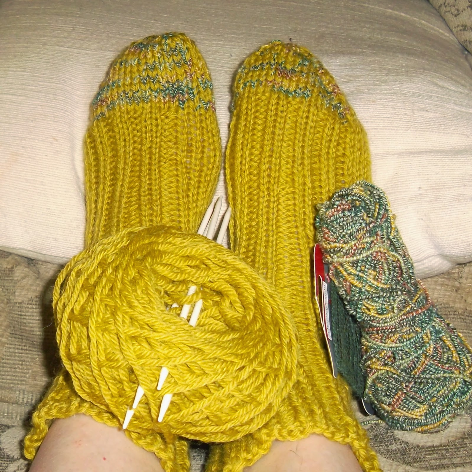 Feet enclosed in hand-knit, yellow-green socks. A yellow-green ball of yarn with four double-pointed knitting needles is positioned on top of the feet. Next to them are a skein of dark-green nylon thread wrapped on cardboard and a larger skein of varigated green, brown and gold yarn.