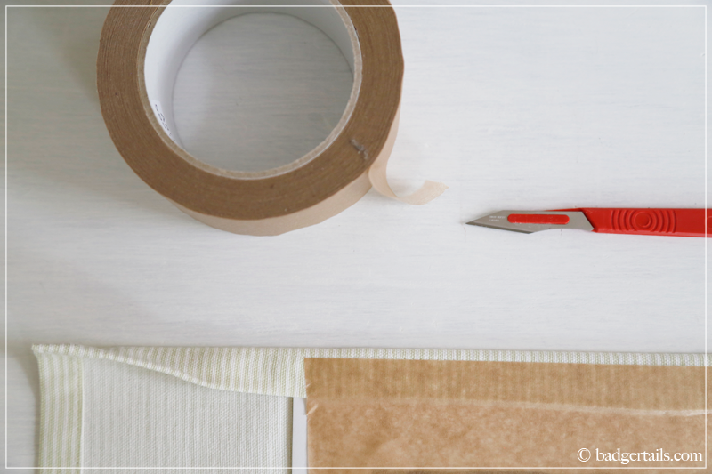 How to Frame a Tea Towel - Securing the fabric with framers tape