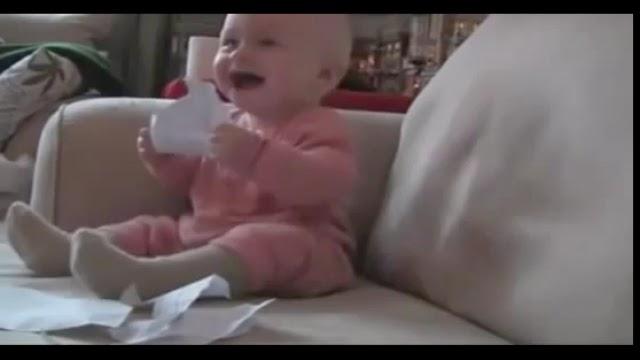 Fou rire d'un bébé devant son père déchirant du papier