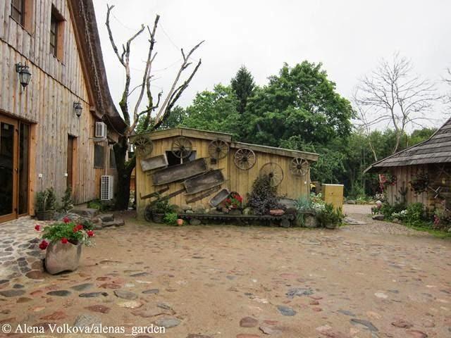 корчма в Литве, деревенский стиль, герань в кашпо, растения в подвесных кашпо, деревянный дом, светильник, старые колеса, на стене, корыта на стене, брусчатка, каменный двор