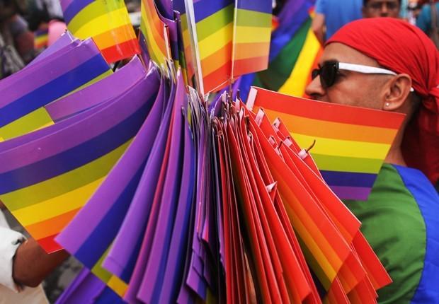 Ativista distribui bandeiras de arco-íris durante parada do orgulho LGBT em Calcutá, na Índia, neste domingo (15). Segundo a France Presse, mais de 500 pessoas das comunidades lésbica, gay, bissexual, travestis e transexuais, além de simpatizantes, participaram do evento anual de conscientização (Foto: Dibyangshu Sarkar/France Presse)