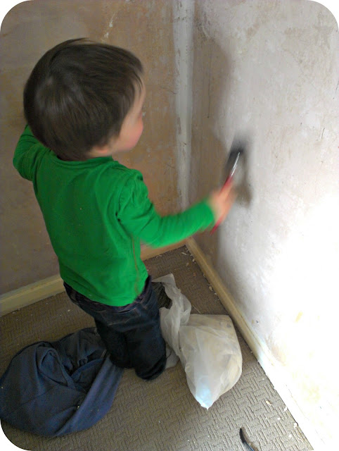 Small boy painting the plaster with water