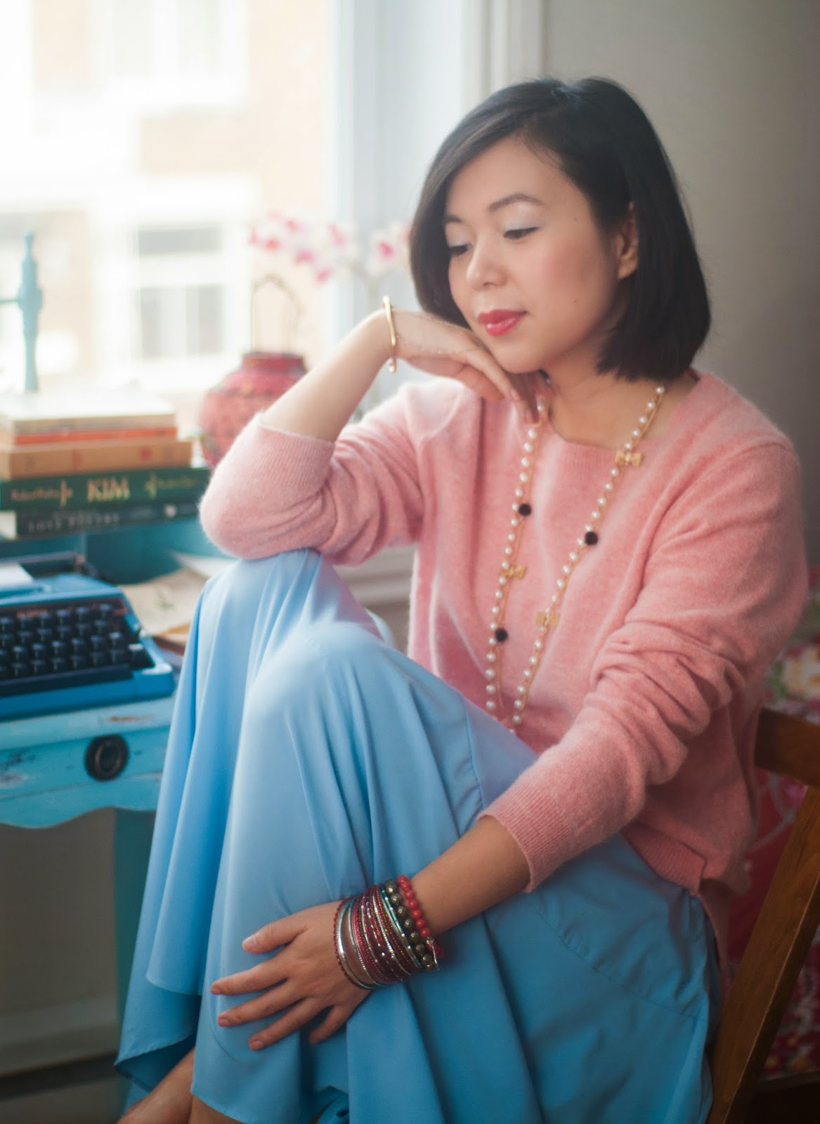 pink fuzzy sweater blue skirt typwriter winter
