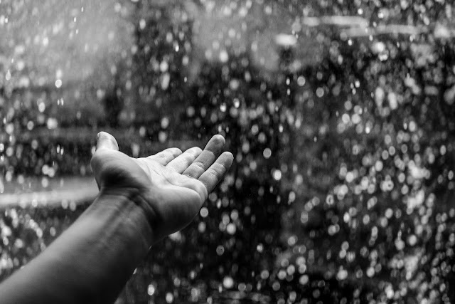 Random black and white photo of rain drops falling in hand