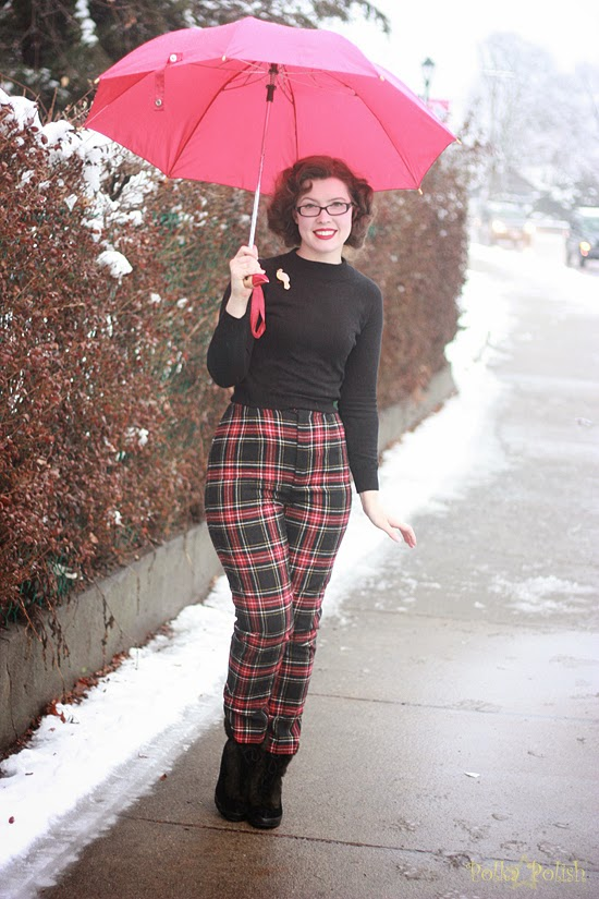 Fall or winter outfit with plaid cigarette pants, black sweater, and a red umbrella