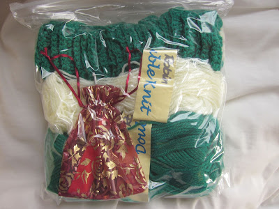 ziploc bag containing green and cream wool and a little red bag