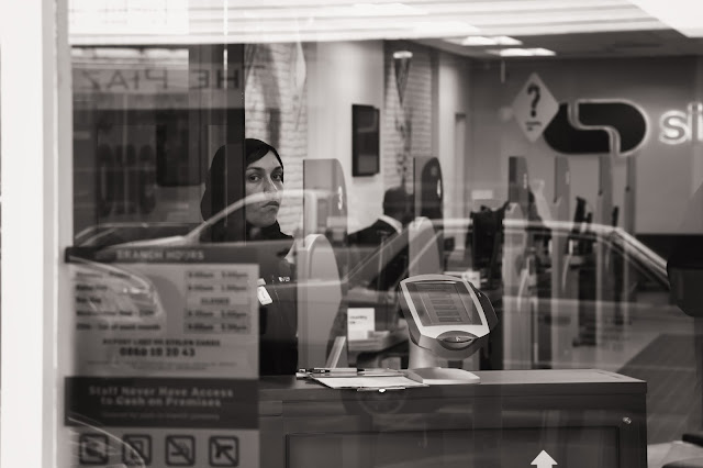 A receptionist in a bank stands at her counter in this street photograph